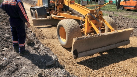leveler: Grader working at road construction site and worker