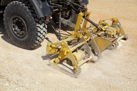 compacting: Road compactor tool compacting gravel at road construction site
