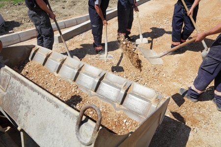 blue collar: Workers team throw gravel into bulldozer bucket with shovels