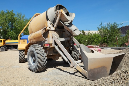 cement pile: Concrete mixer at road construction site with heap of gravel