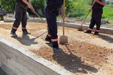 Workers team throw gravel  with shovels at road construction