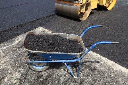 asphalt paving: Barrow with asphalt and road roller at road construction site Stock Photo