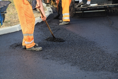 gravel roads: Workers making asphalt with shovels at road construction