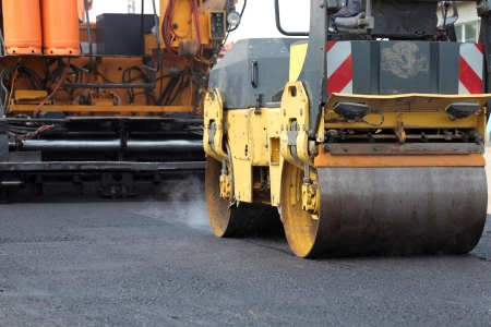 roller compactor: Road roller and asphalt paving machine at construction site