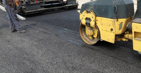 roadwork: Road roller and asphalt paving machine at construction site