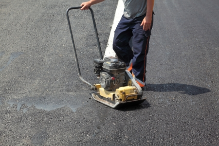asphalt paving: Worker with compactor at a road construction site