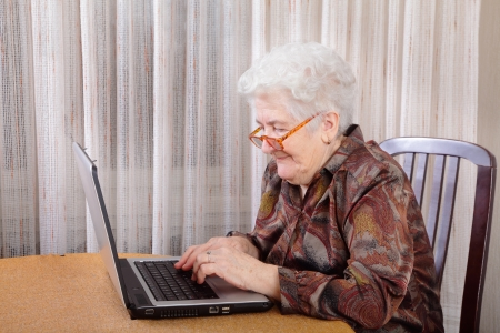 Portrait of a senior woman working at computer photo