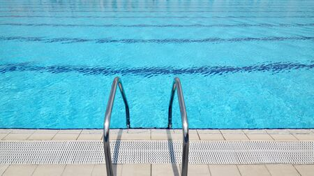 Steel ladder at open air olympic swimming pool photo
