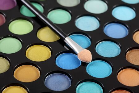 Make-up brush at colorful eye shadows palette photo