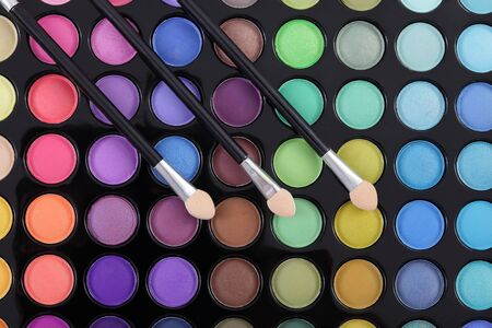 Make-up brushes at colorful eye shadows palette photo