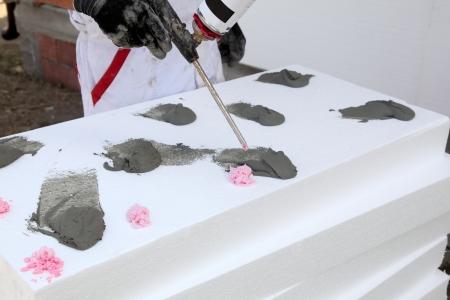 Worker applying glue on thermal insulation styrofoam panels