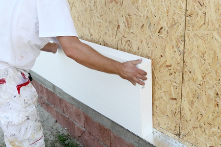 insulating: Worker placing polystyrene sheet insulation to the wall Stock Photo