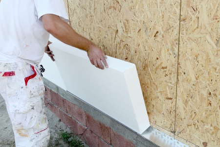 insulating: Worker placing styrofoam sheet insulation to the wall