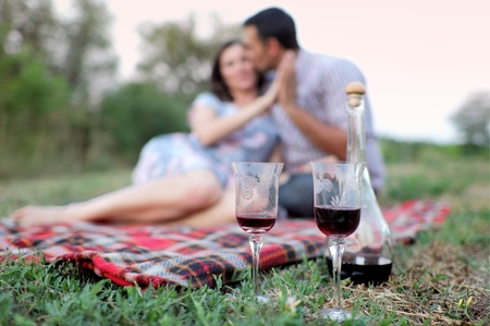 Glasses with wine with young couple in background photo