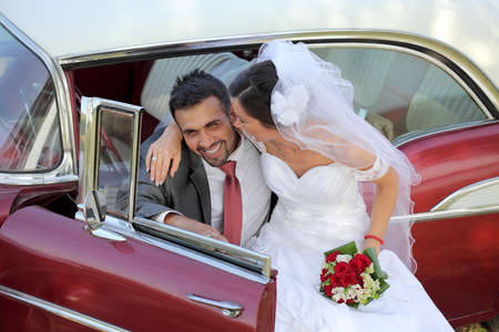 Bride and groom with a vintage car photo