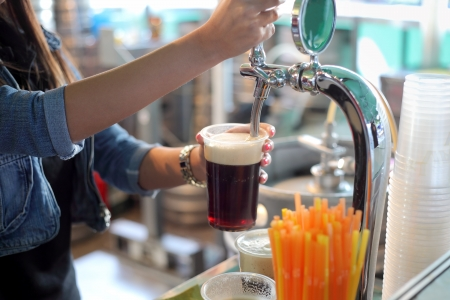 Pouring dark beer to plastic glass from beer tap photo