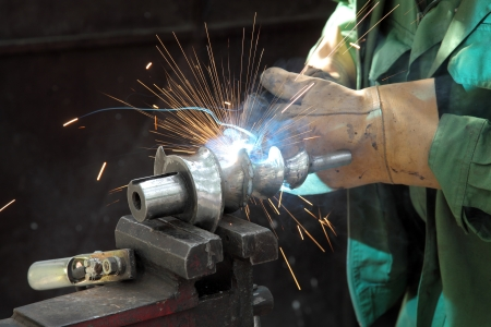 Closeup photo of arc welding of a steel shaft with helicoid photo