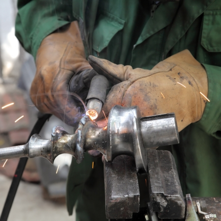 Closeup photo of arc welding of a steel shaft with helicoid Stock Photo
