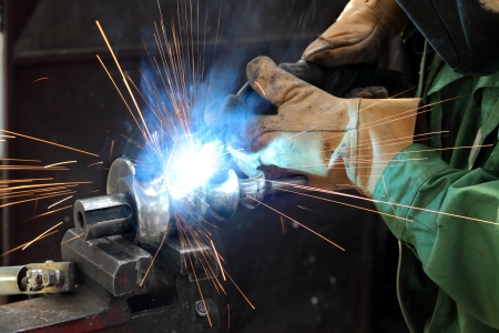 welding metal: Closeup photo of arc welding of a steel shaft with helicoid Stock Photo