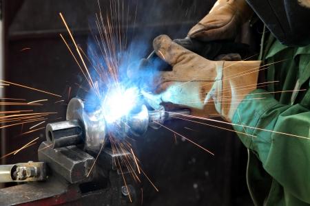 soldador: Foto del primer de la soldadura por arco de un eje de acero con helicoide Foto de archivo