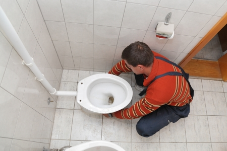 Plumber replacing broken toilet in a washroom Stock Photo - 15832532