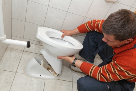 Plumber replacing broken toilet in a washroom photo