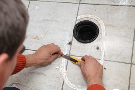 Plumber replacing broken toilet in a washroom, cutting of silicone glue Stock Photo - 15832533