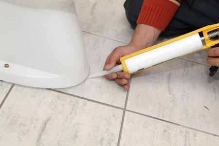 caulking: Plumber fixing toilet in a washroom with  silicone cartridge