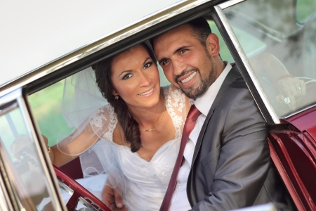 Bride and groom in a vintage car photo
