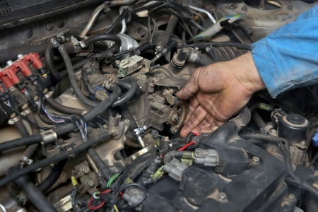 throttle: Servicing of LPG converted car engine, worker checking throttle