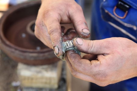 lubrication: Mechanic lubricate a roller bearing with lithium grease