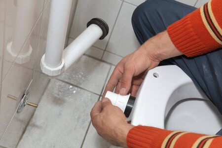 Plumber fixing plastic tube of wall mounted toilet cistern Stock Photo - 16083648