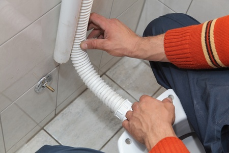 Plumber fixing plastic tube of wall mounted toilet cistern Stock Photo - 16083651
