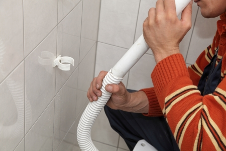 Plumber fixing plastic tube of wall mounted toilet cistern photo