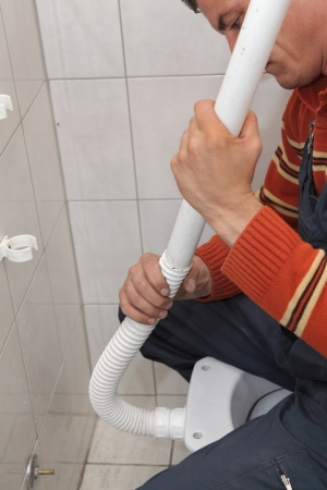 Plumber fixing plastic tube of wall mounted toilet cistern Stock Photo - 16036731