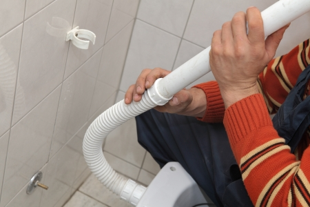 Plumber fixing plastic tube of wall mounted toilet cistern Stock Photo - 16083615