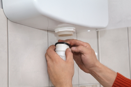 Plumber fixing wall mounted toilet cistern photo