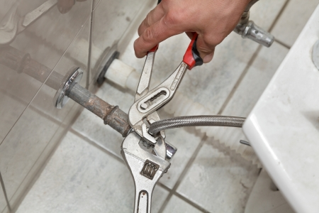 Plumber fixing water pipe of tap on bidet in washroom Stock Photo - 16083570
