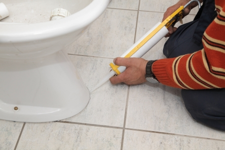 caulking: Plumber fixing bidet in a washroom with  silicone cartridge