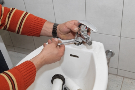 Plumber fixing water tap on bidet in a washroom photo