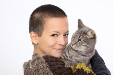 Young smiling woman hold gray domestic cat photo