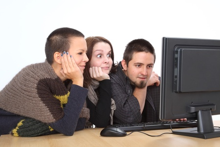 Three young relaxed Caucasian people looking to computer photo