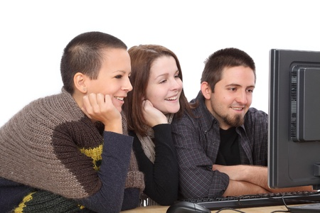 Three young smiling Caucasian people looking to computer Stock Photo - 16194343