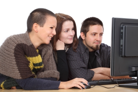 Three young smiling Caucasian people looking to computer photo