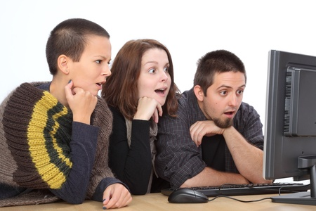 Three young surprised Caucasian people looking to computer Stock Photo - 16194350