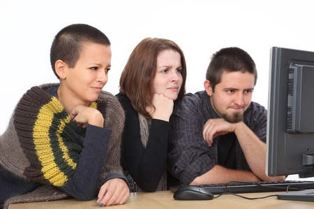 Three young shocked Caucasian people looking to computer photo