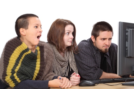 Three young surprised Caucasian people looking to computer photo