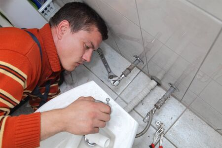 Plumber fixing water tap on bidet in a washroom Stock Photo - 17008144