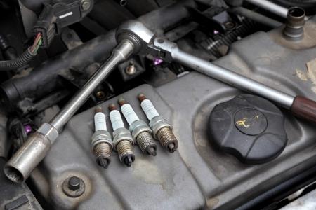 servicing: Modern car gasoline engine servicing,  ratchet tool and spark plug