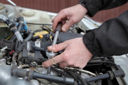Modern car gasoline engine servicing, workers hands, ratchet and spark plug